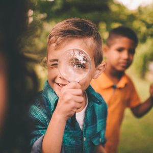 Portrait of a little boy holding up a large round magnifying glass to his face, making his eye look humourously large, while playing with friends in a summer park